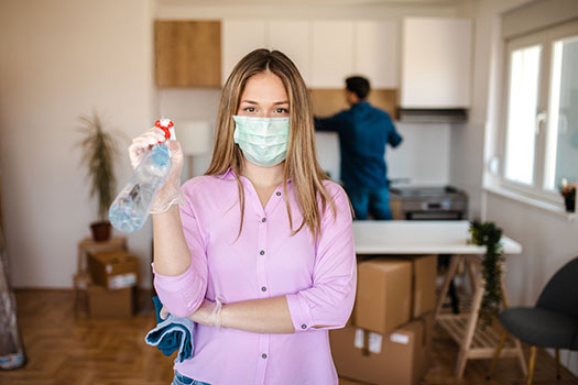 Young woman cleaning her house during COVID-19